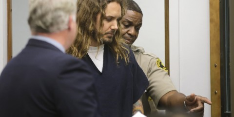 Tim Lambesis (C), lead singer for the heavy metal band As I Lay Dying, enters the courtroom for his arraignment in San Diego North County court in Vista, California May 9, 2013. Lambesis was arrested in California on Tuesday on charges that he sought the help of an undercover detective to have his estranged wife killed, police said. Lambesis was taken into custody in Oceanside, near San Diego, said San Diego County Sheriff's Department spokeswoman Jan Caldwell.    REUTERS/Lenny Ignelzi/Pool  (UNITED STATES - Tags: CRIME LAW SOCIETY ENTERTAINMENT) - RTXZGTD